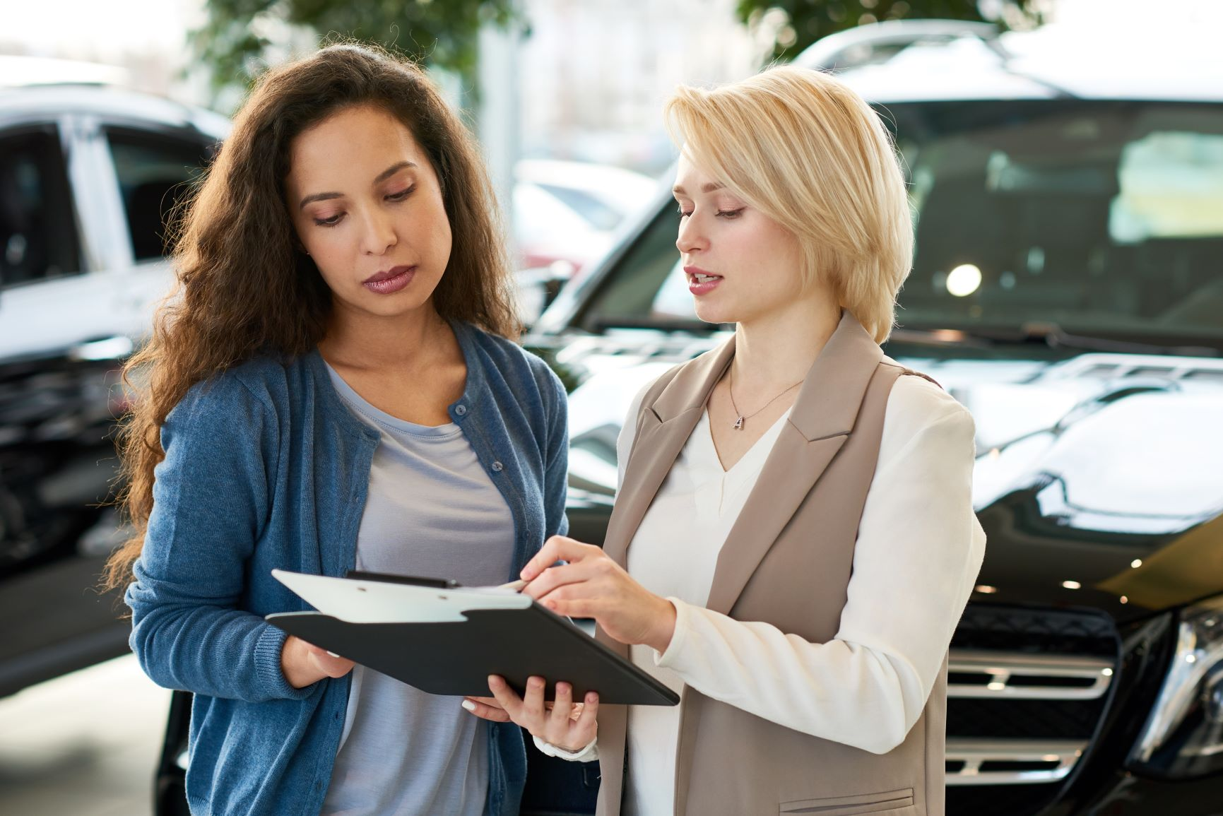 two women going over car paperwork