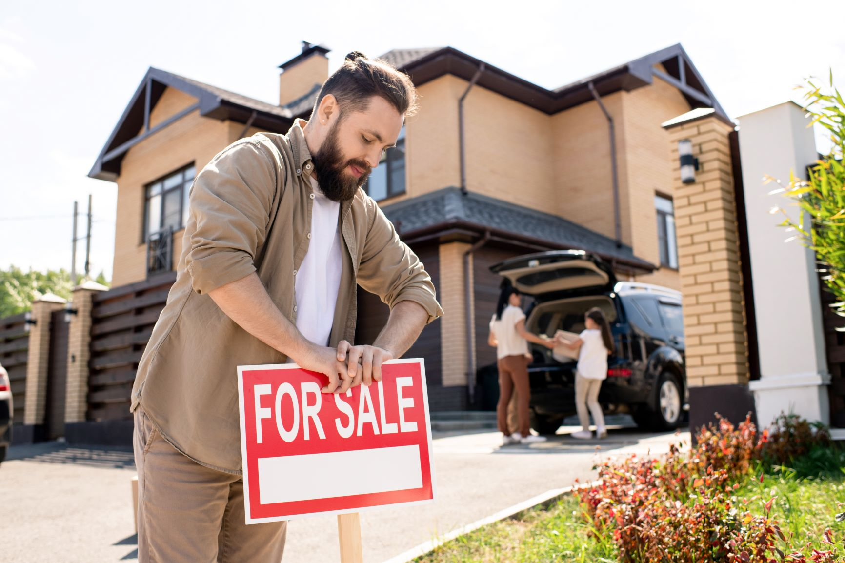 man putting for sale sign in front of house