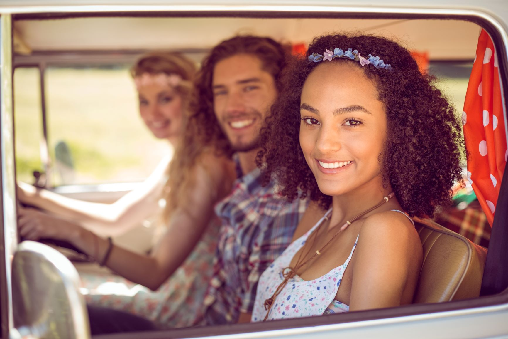 three young people sitting in front of car
