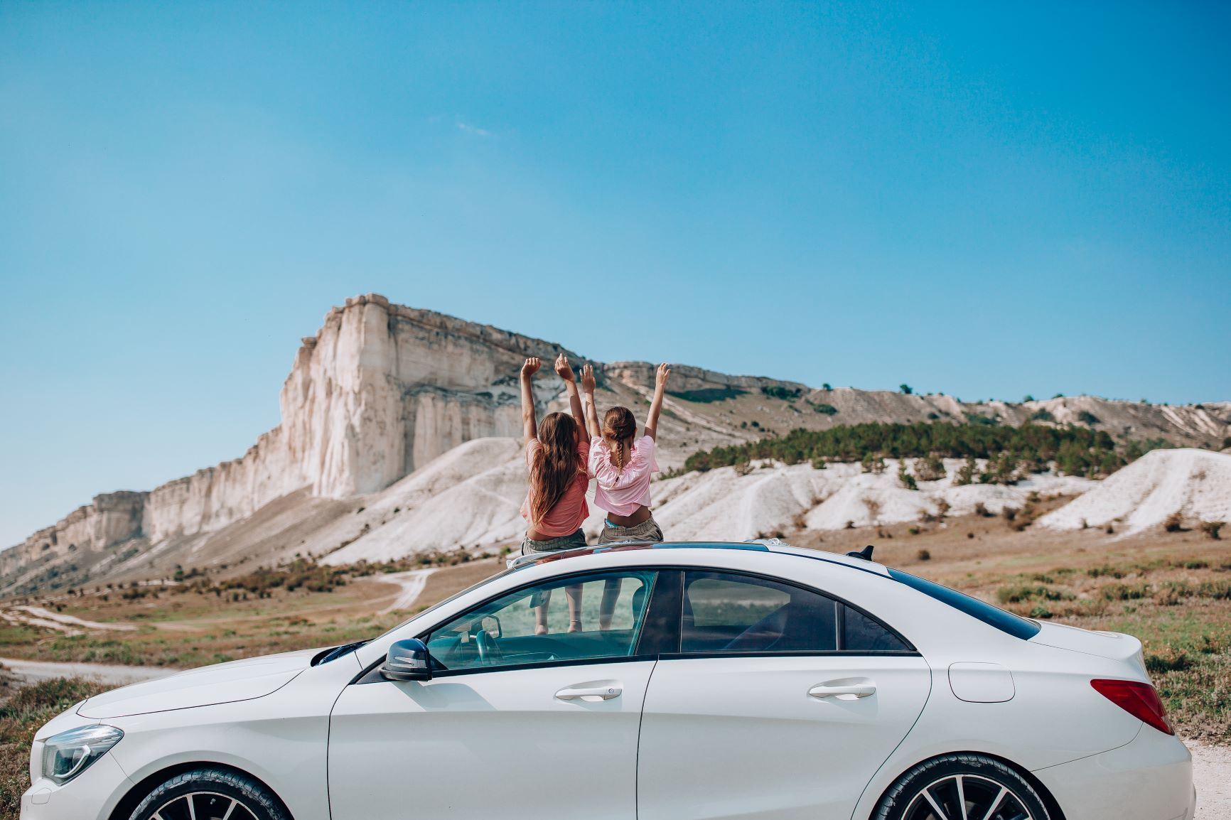 two girls sitting on top of car