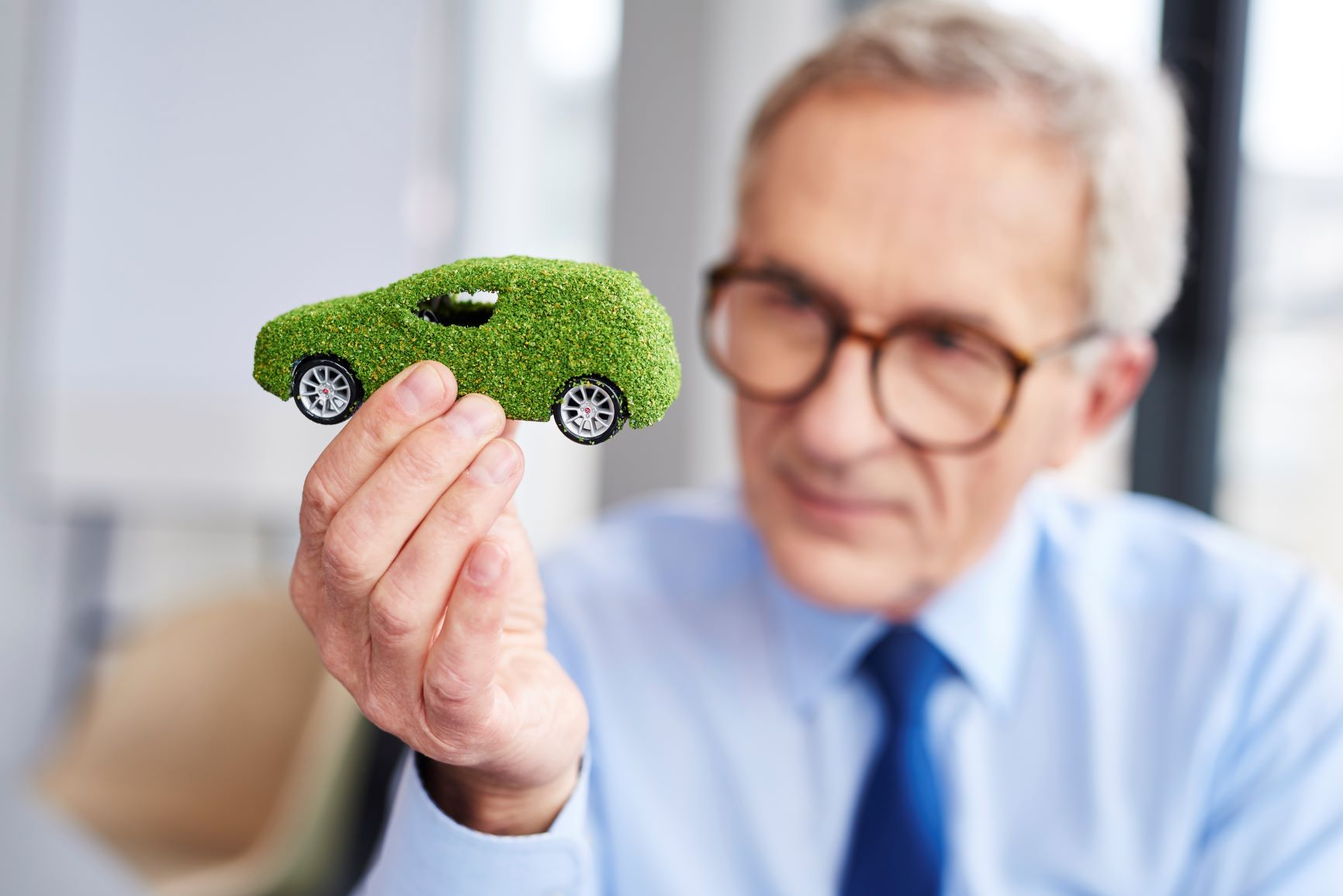 man holding up green eco friendly car