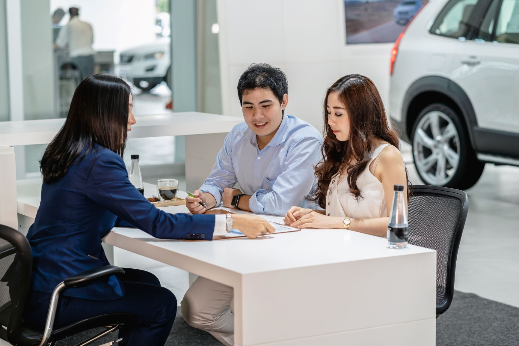couple signing a contract at a car dealership