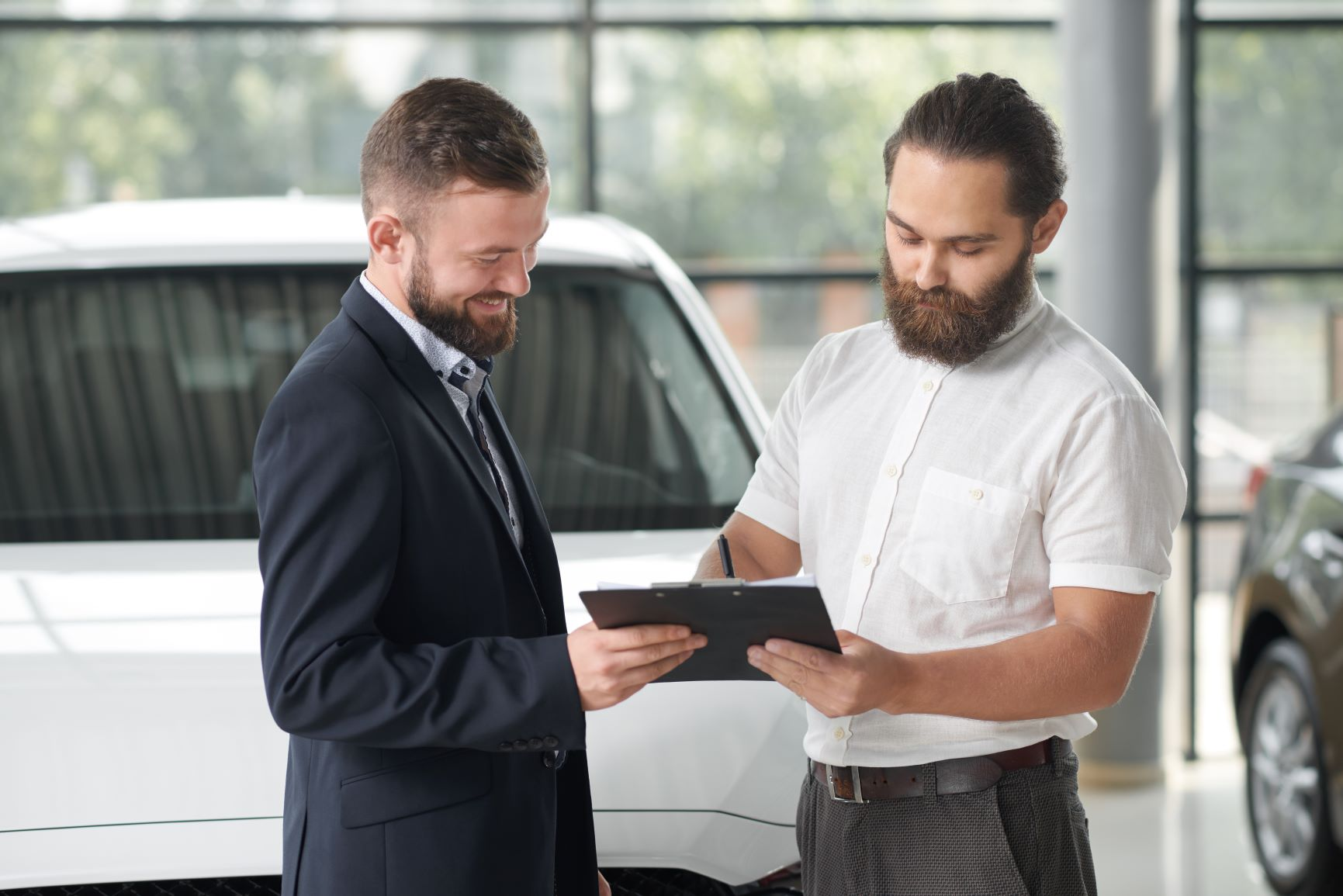 man signing car contract in a dealership