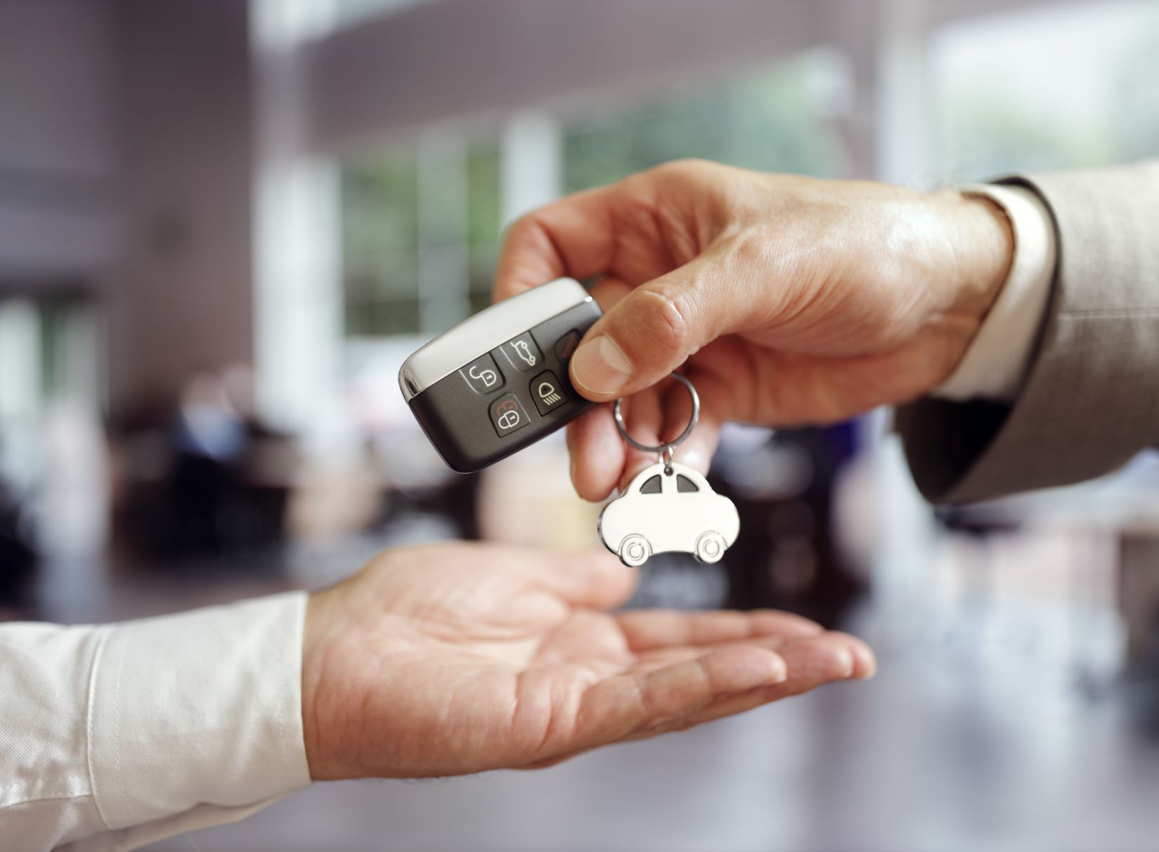 car salesman handing car keys