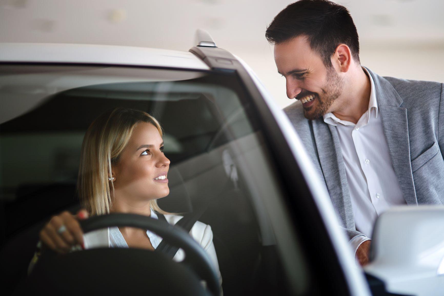 car salesman talking to blonde woman in car