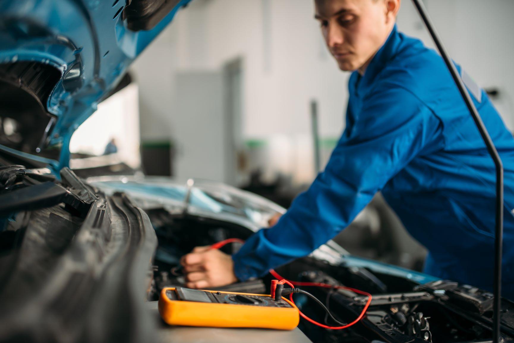 mechanic working on car battery