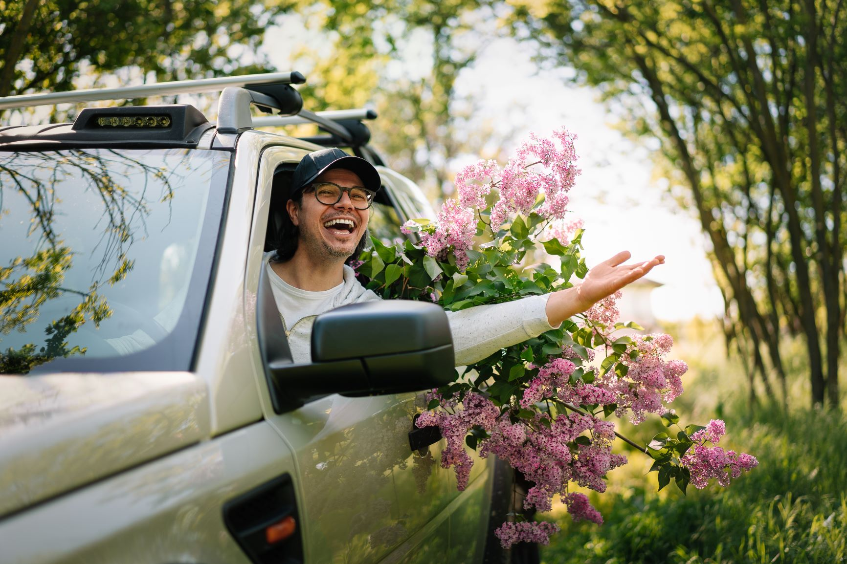 Man driving a car with the window down smiling by flowers