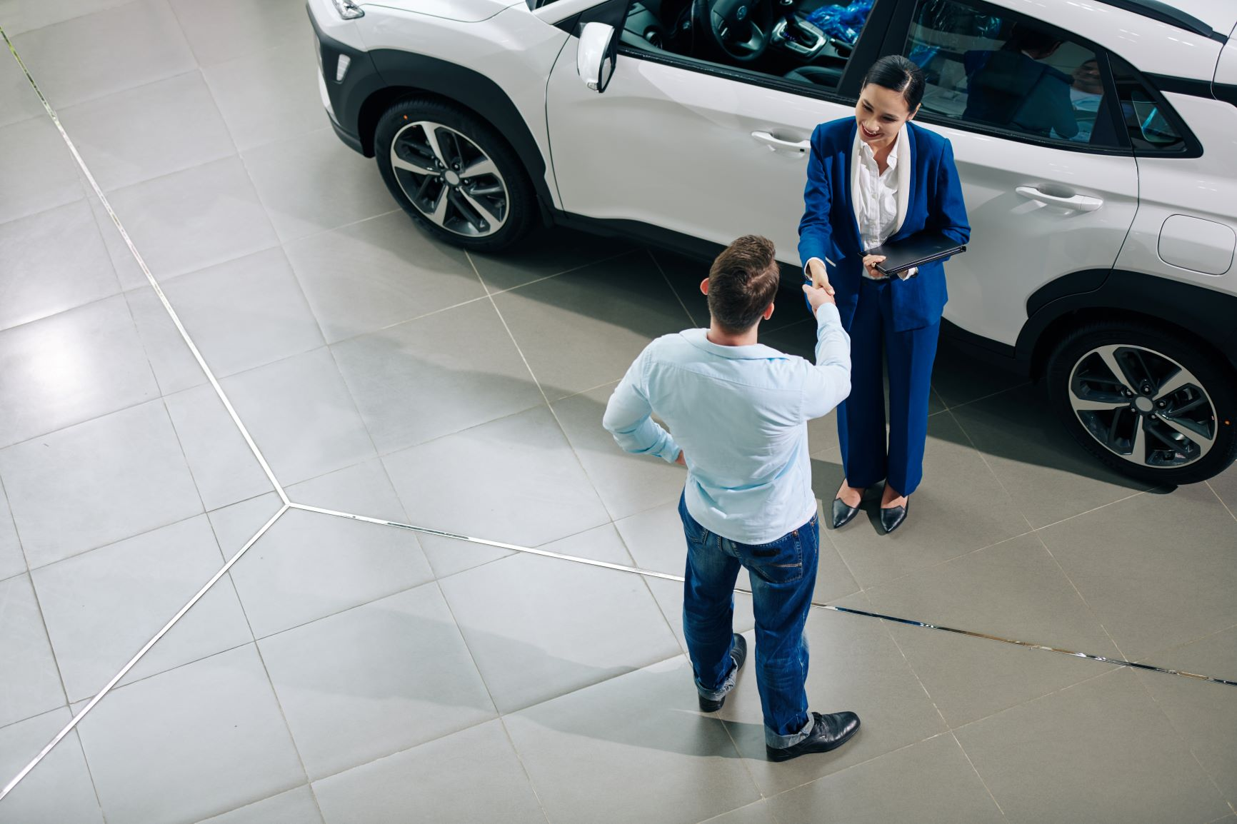 female car salesperson talking to man at dealership