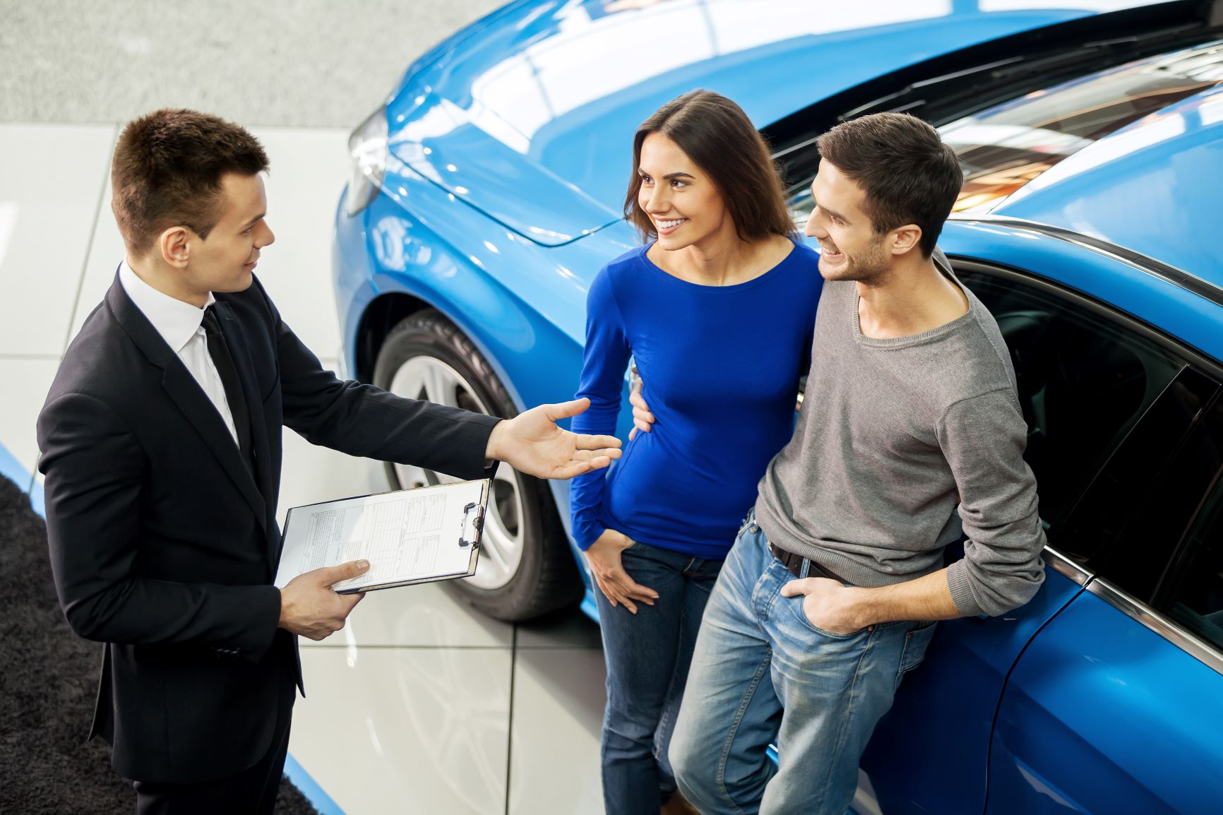 couple talking to car salesman in front of blue car