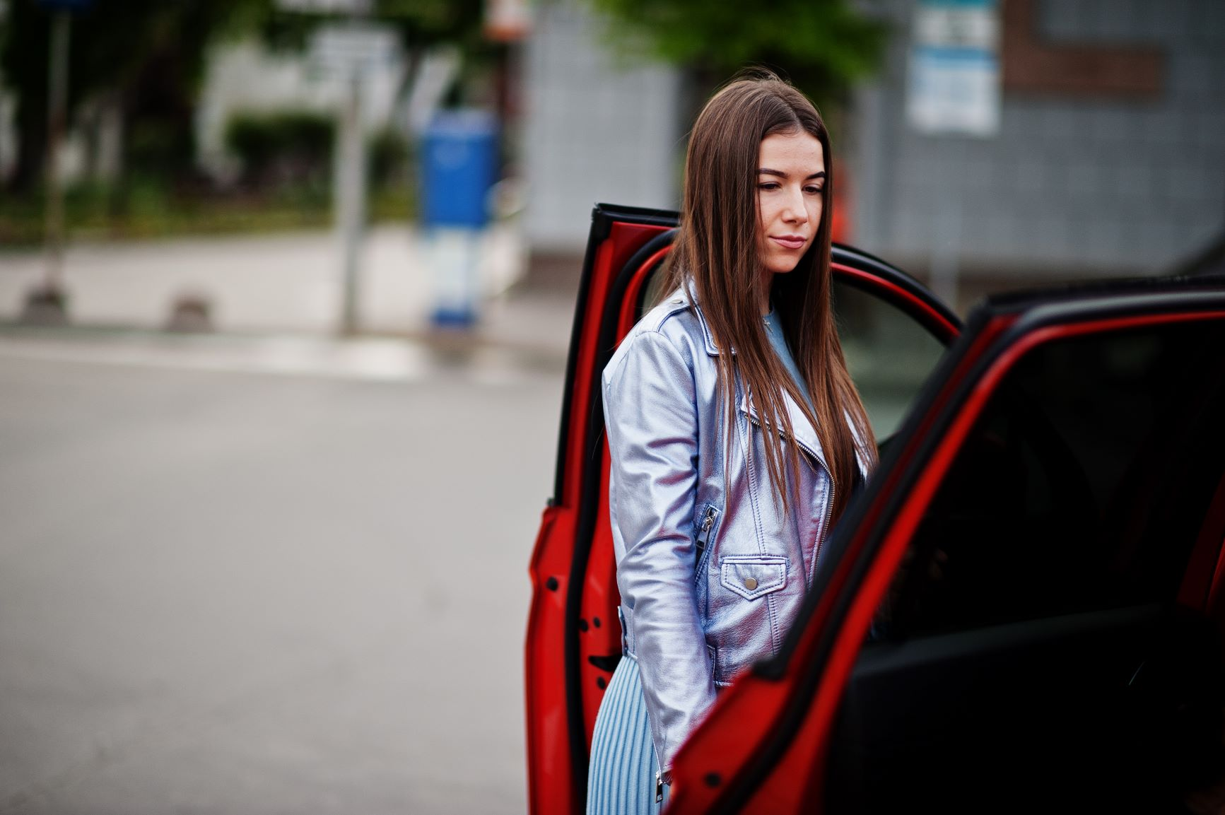 woman standing next to red car