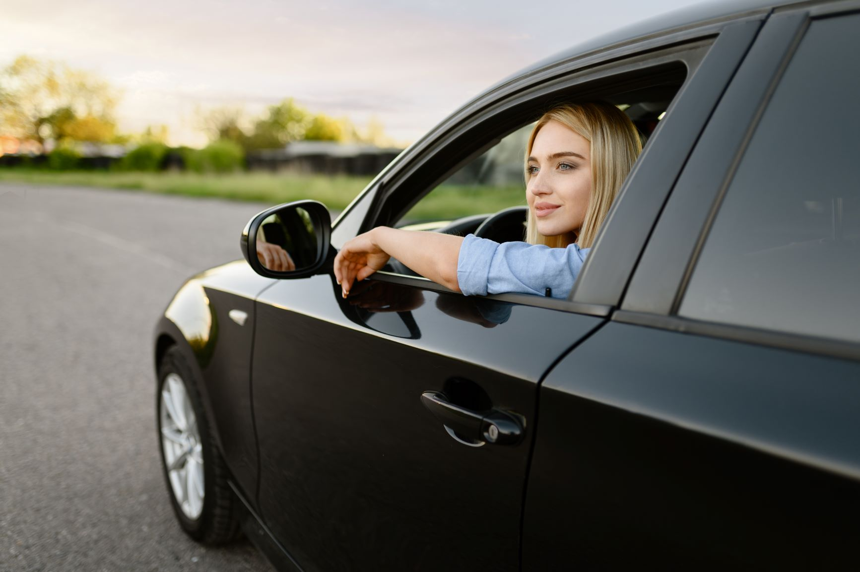 blonde woman looking outside of her car