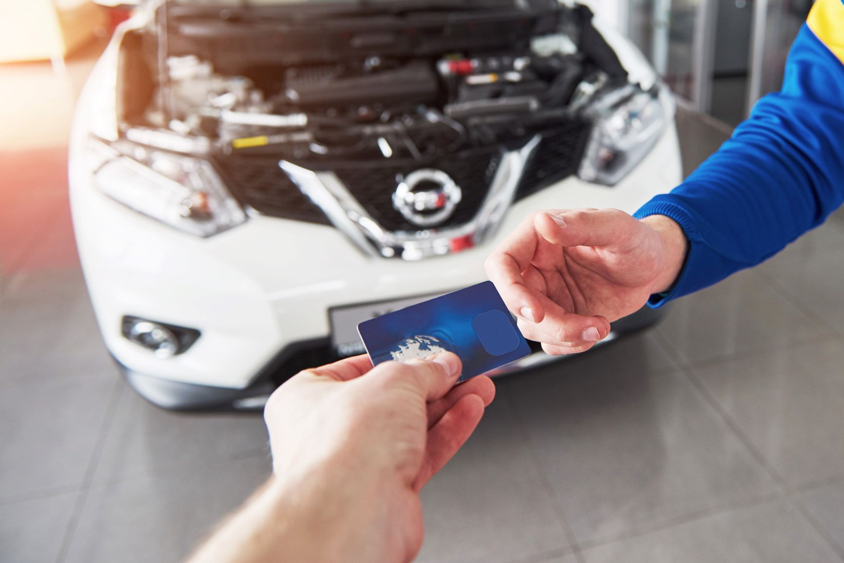 handing a credit card to a mechanic in front of car