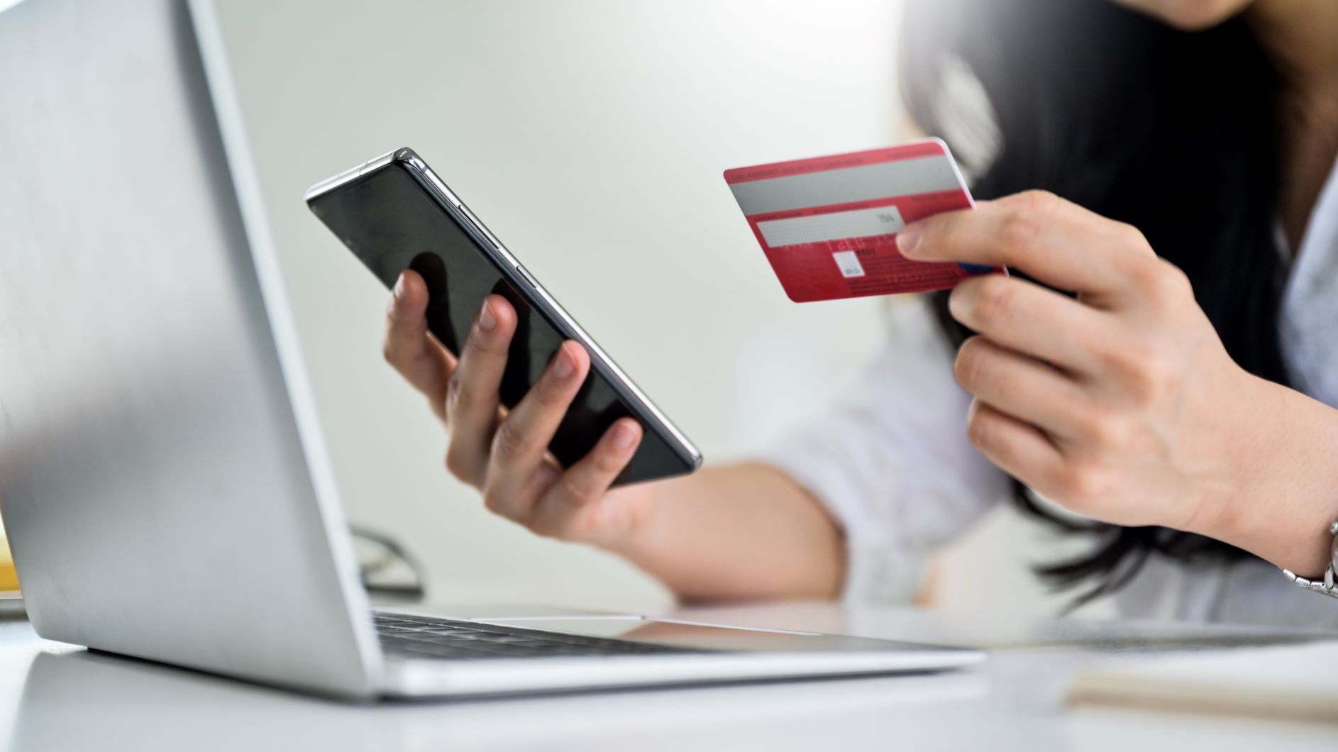 woman holding credit card and phone next to laptop