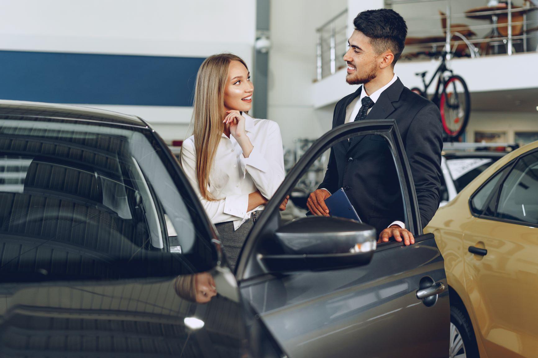 car salesman talking to attractive blonde female customer