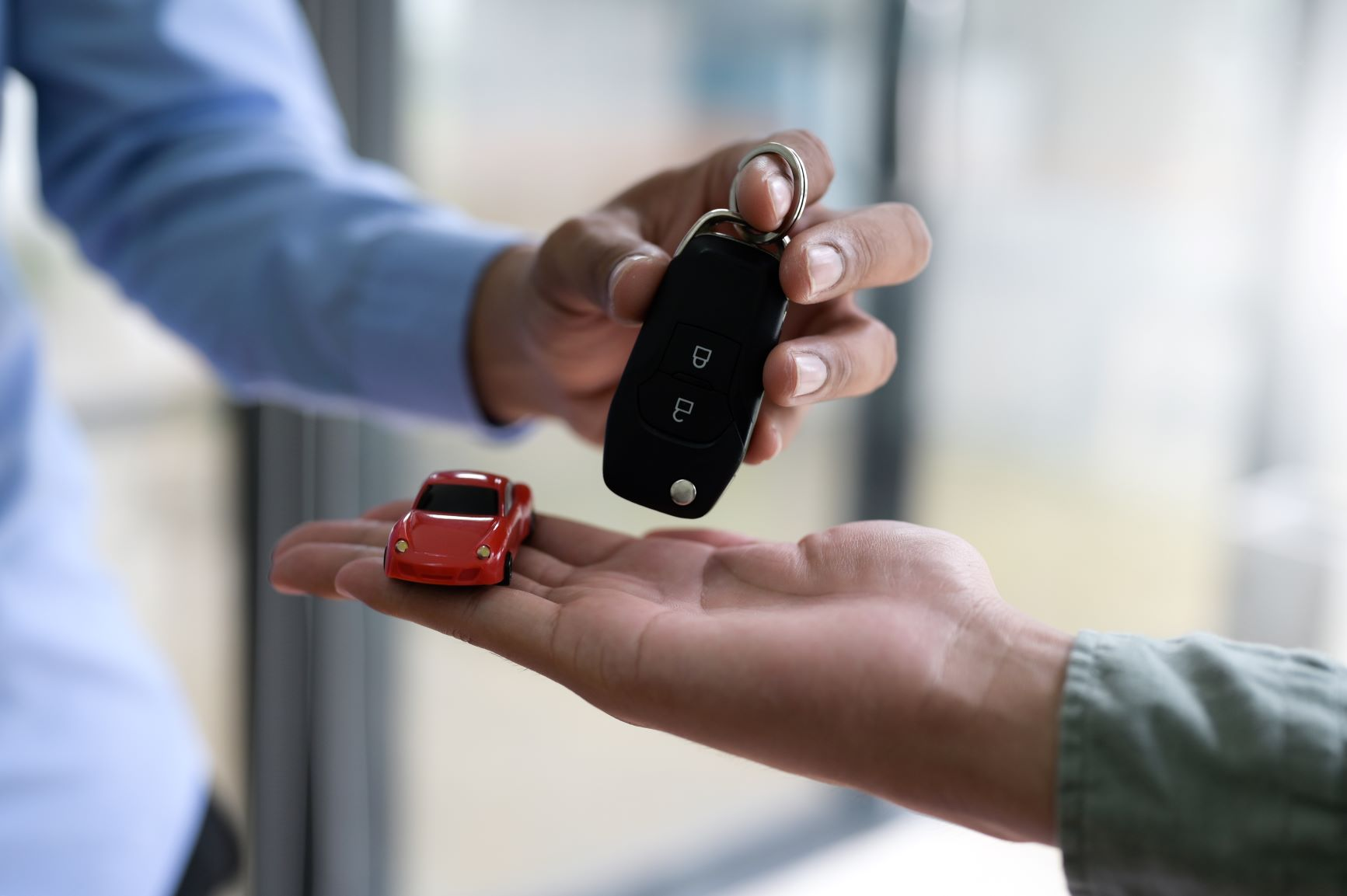 car keys and red toy car with hands in shot