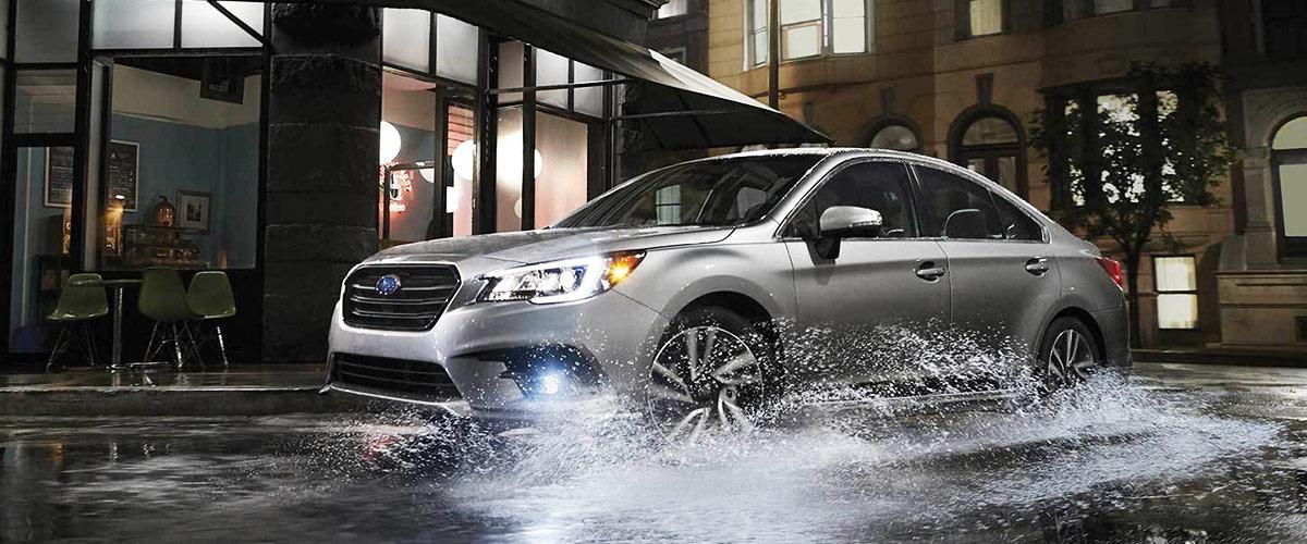 Silver Subaru Legacy in puddle