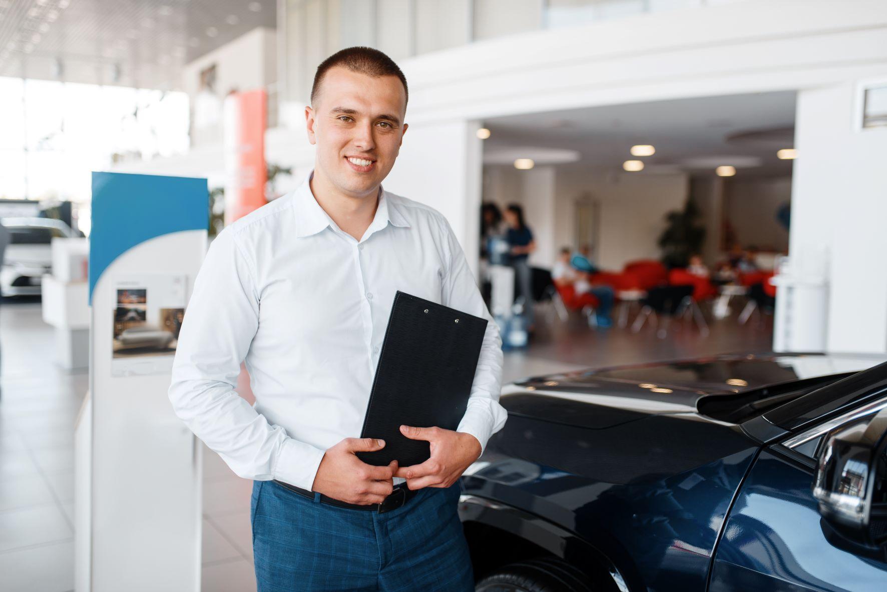 car salesman standing in car dealership
