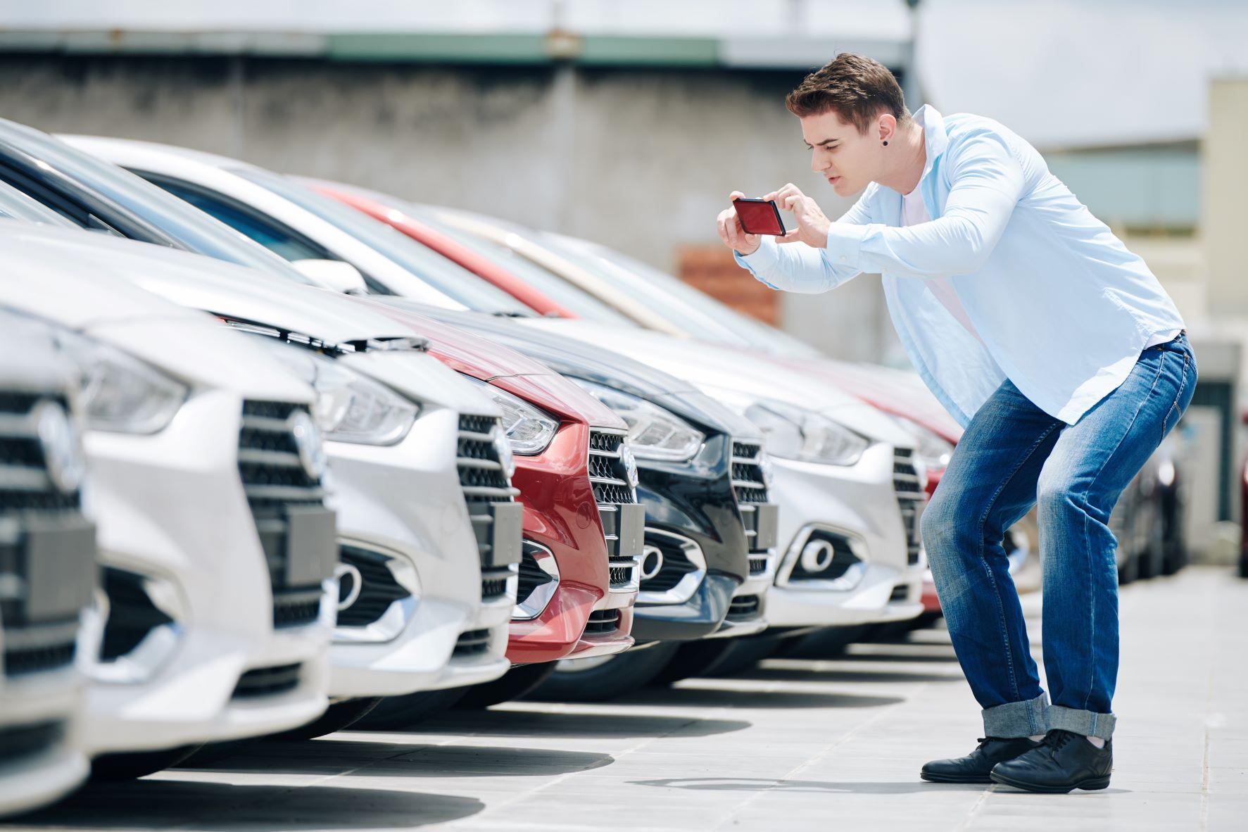 customer at car dealership taking pictures