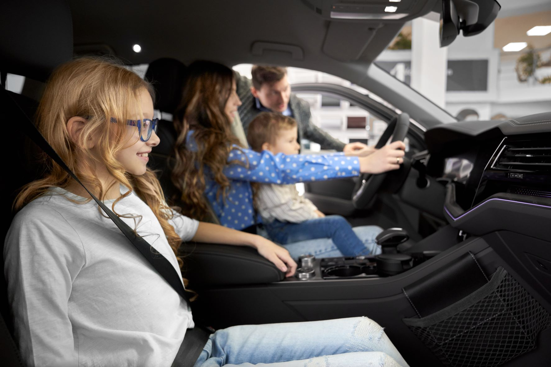 family in car at a dealership
