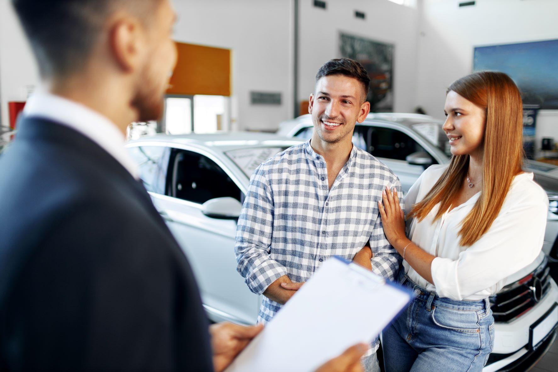 couple talking to car salesman at dealership