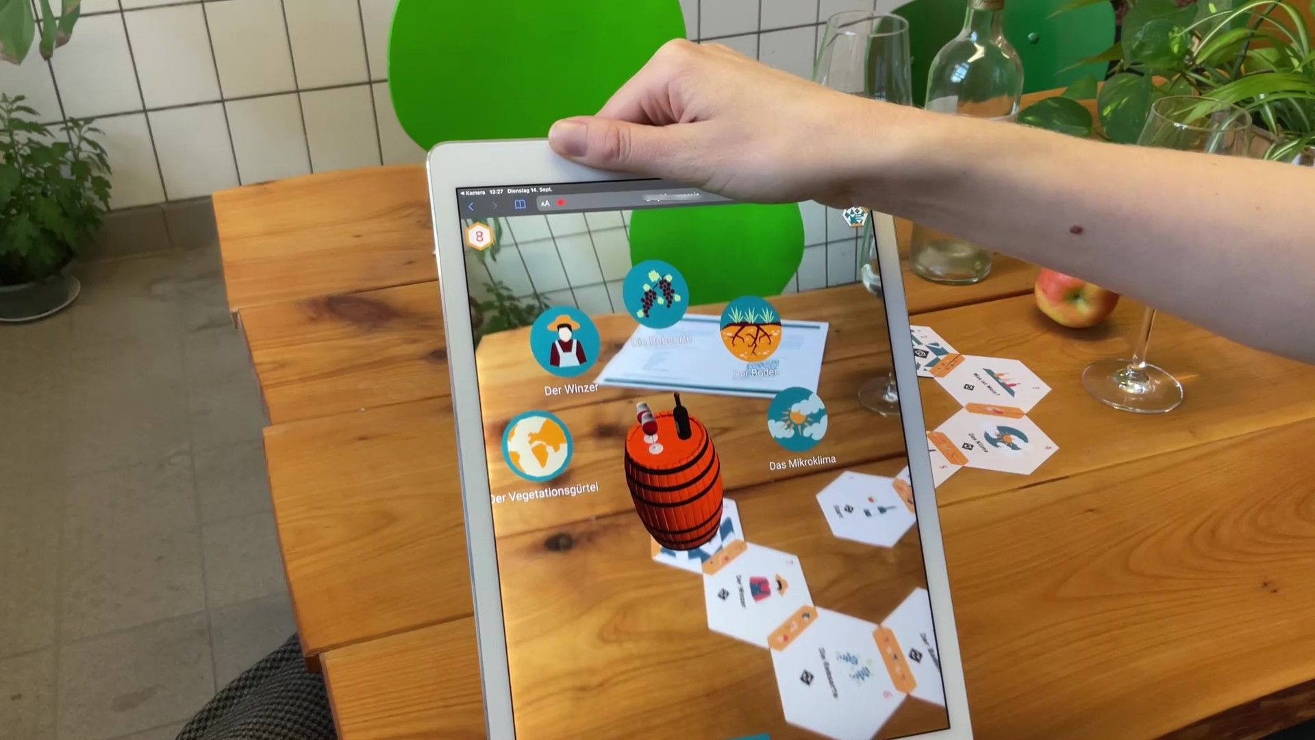 An ipad is hold over a gard game and shows 3D elements popping out of the cards. You can see a wine barrel with several interactive elements around it.