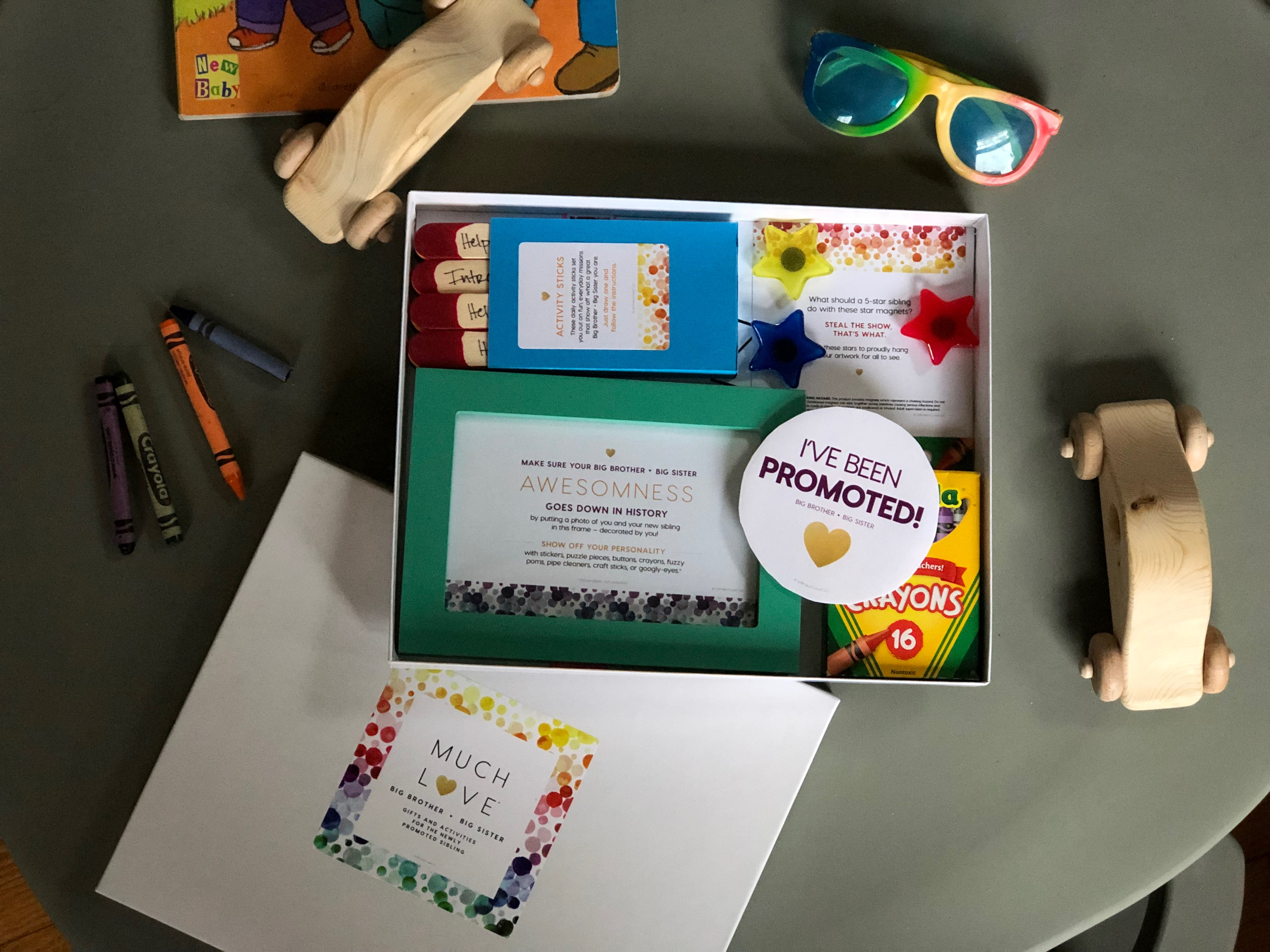 """A gift box in the center with sunglasses and toys around the edge of the box -- in the box are crayons, a """"I've been promoted"""" sticker, activity sticks, and stars."""