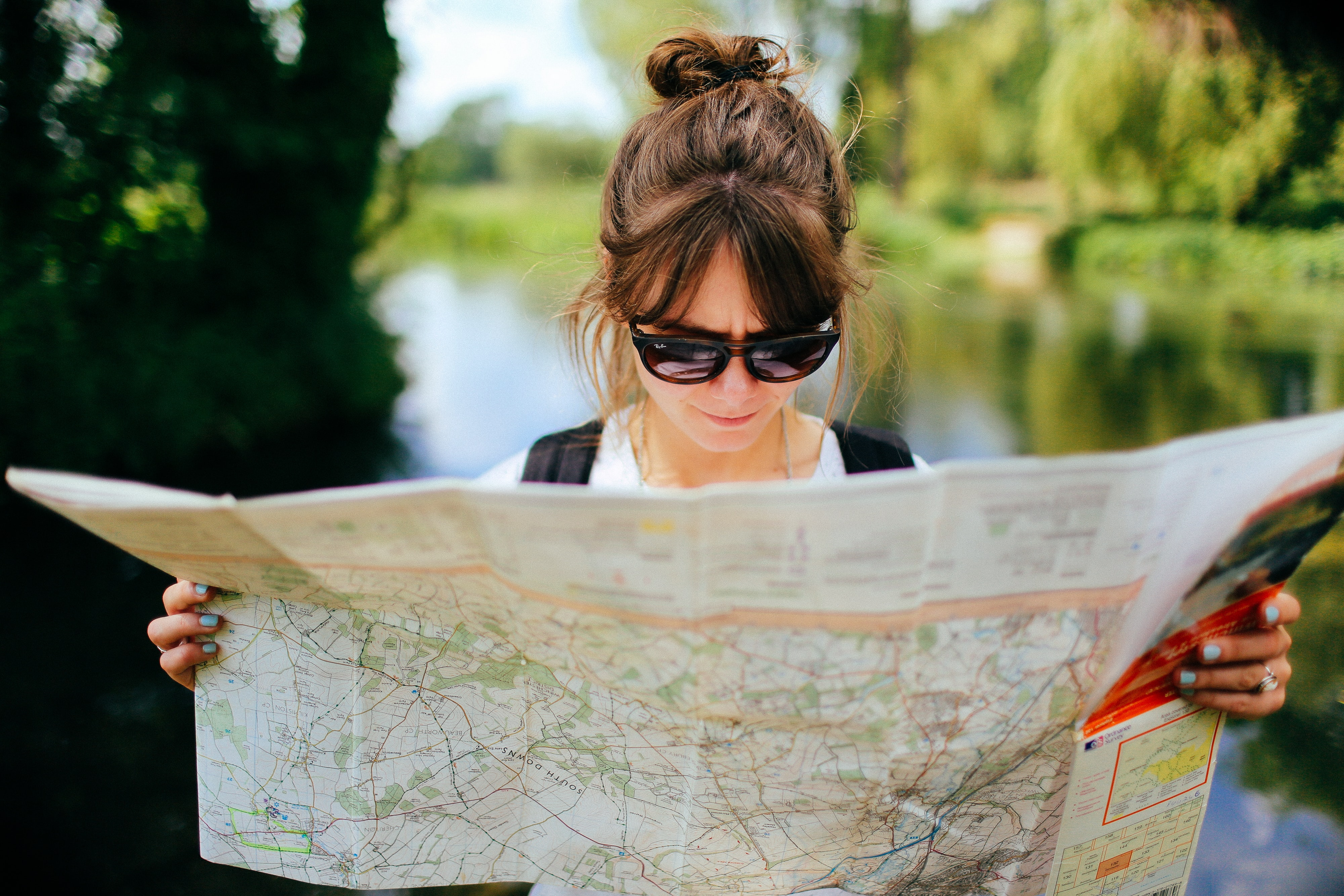 A woman standing outside with green trees and a lake in the background that is blurred, she is wearing sunglasses and she is holding a map open that spans across the entire bottom of the image.