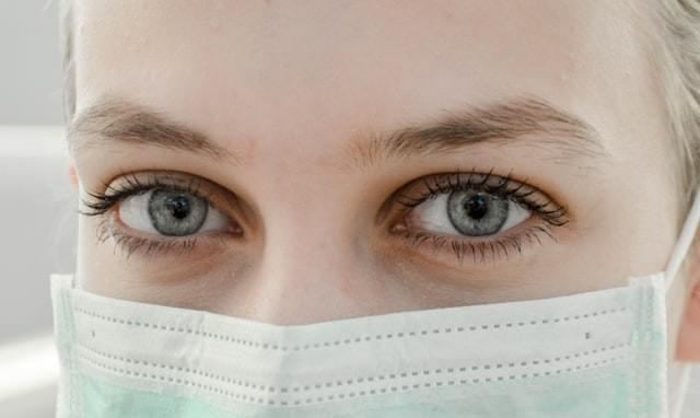 Close image of woman's eyes. She is wearing a medical face mask