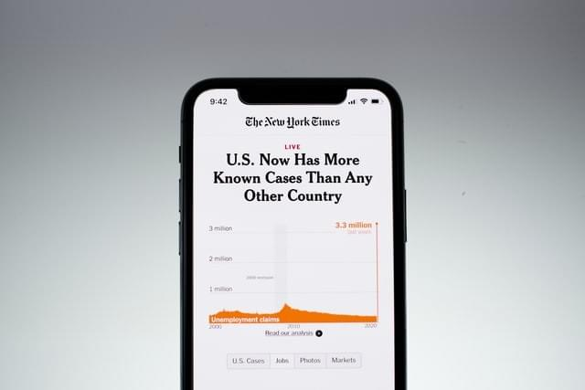 image of a cell phone displaying New York Times article with the headline U.S. Now Has More Known Cases Than Any Other Country