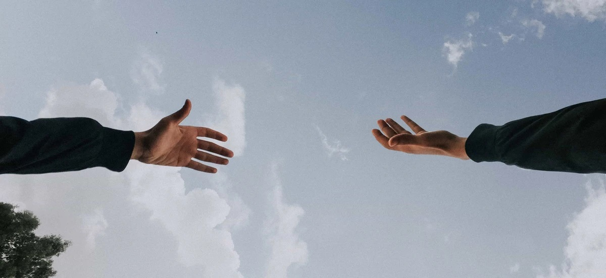 Shot from below, a picture of hands reaching towards each other with the backdrop of a partly cloudy daytime sky
