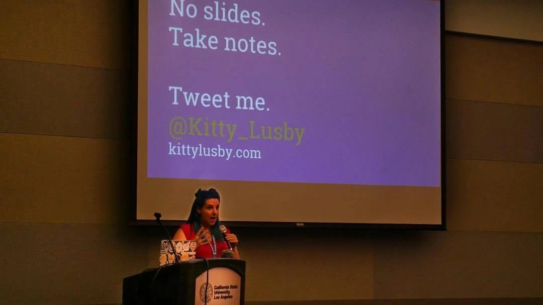 Kitty speaking at an event with a slide that says No Slides, Take Notes, Tweet Me