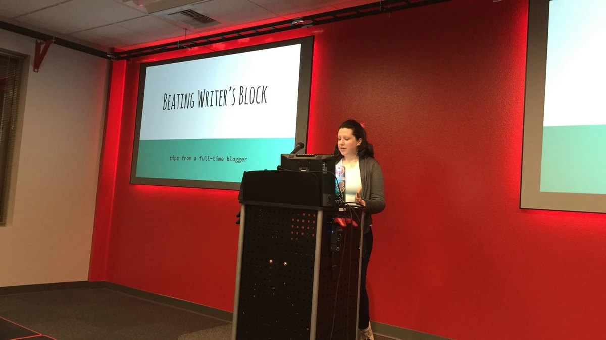 Kitty presenting in front of a bright red wall with a slide that says Beating Writer's Block