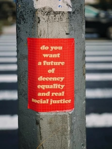 """A pole at a street crossing with a red poster that says """"do you want a future of decency equality and real social justice"""""""