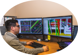 Developer working on building information modeling with dual desktop monitors