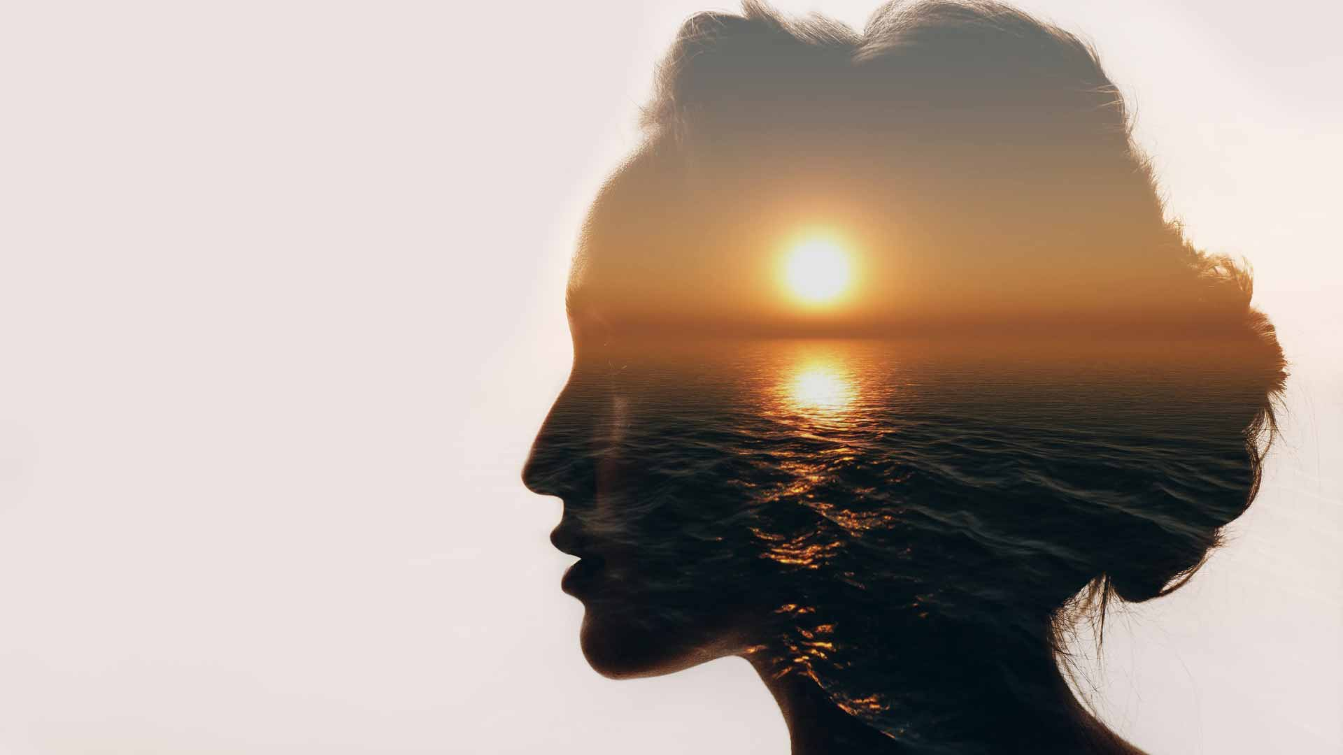 A photo of a woman's head with a sunset imposed in it