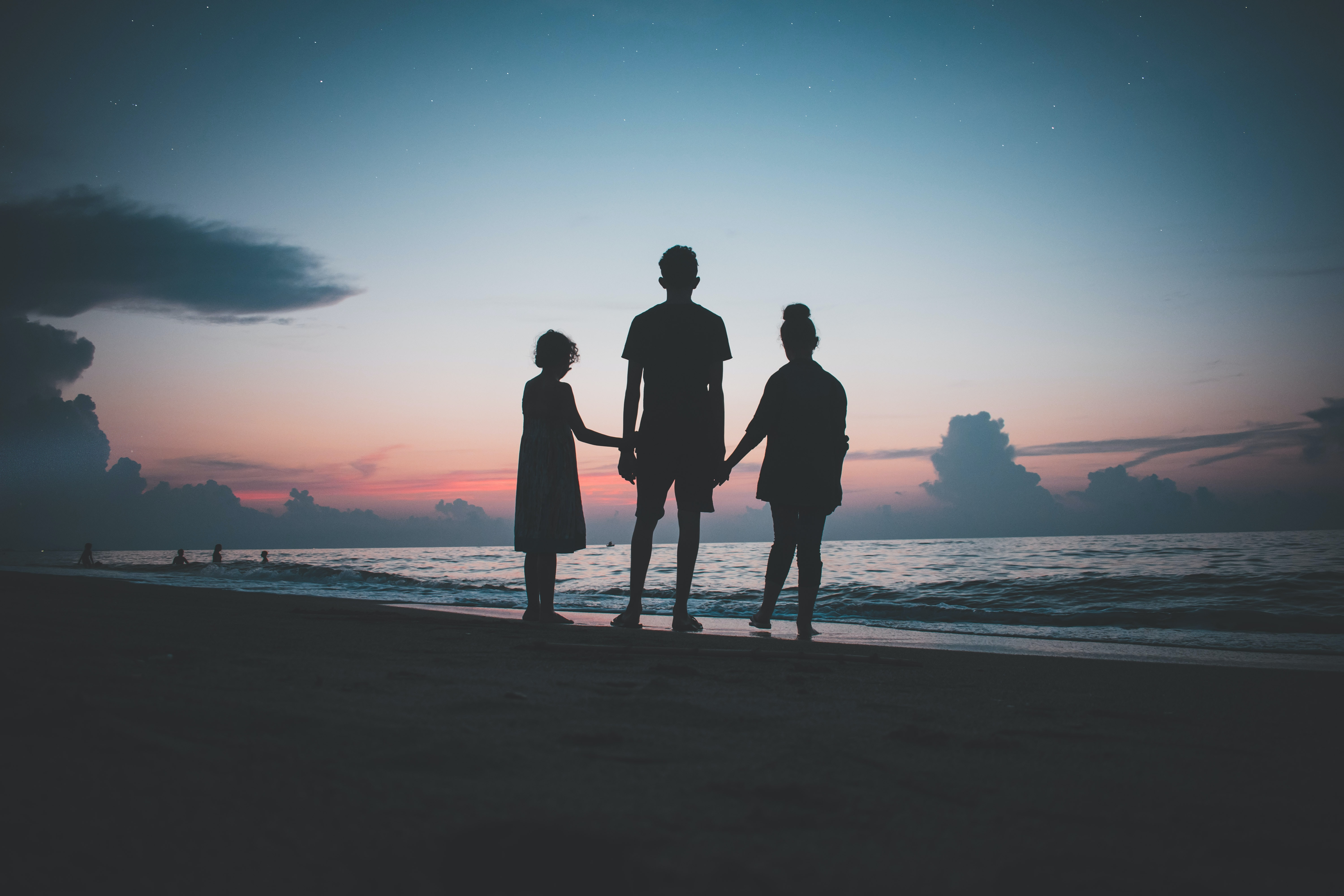 A family holding hands on a beach in front of the ocean during sunset.
