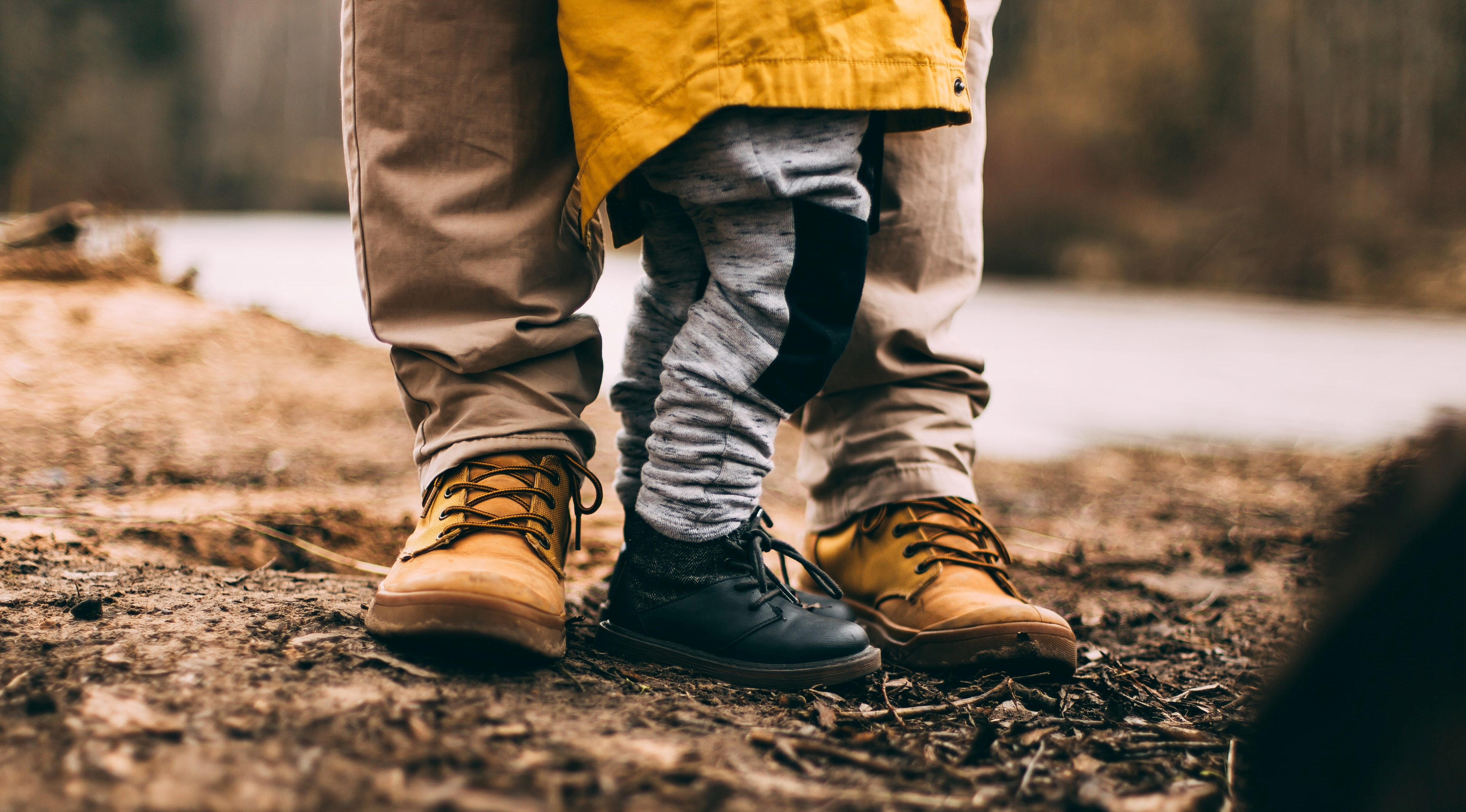 A father and son stand in their work boots.