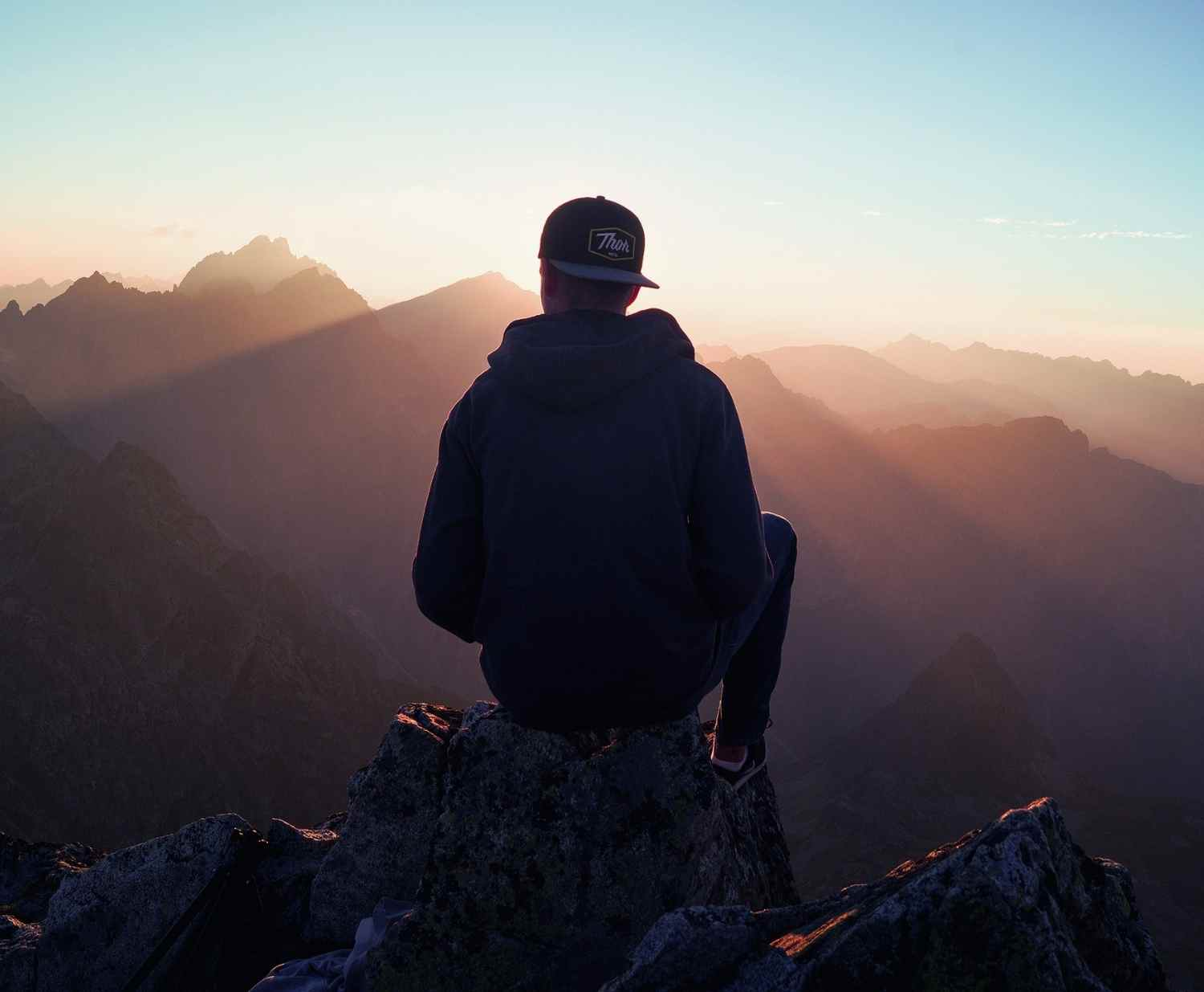 Man sitting on a mountain looking out at a view