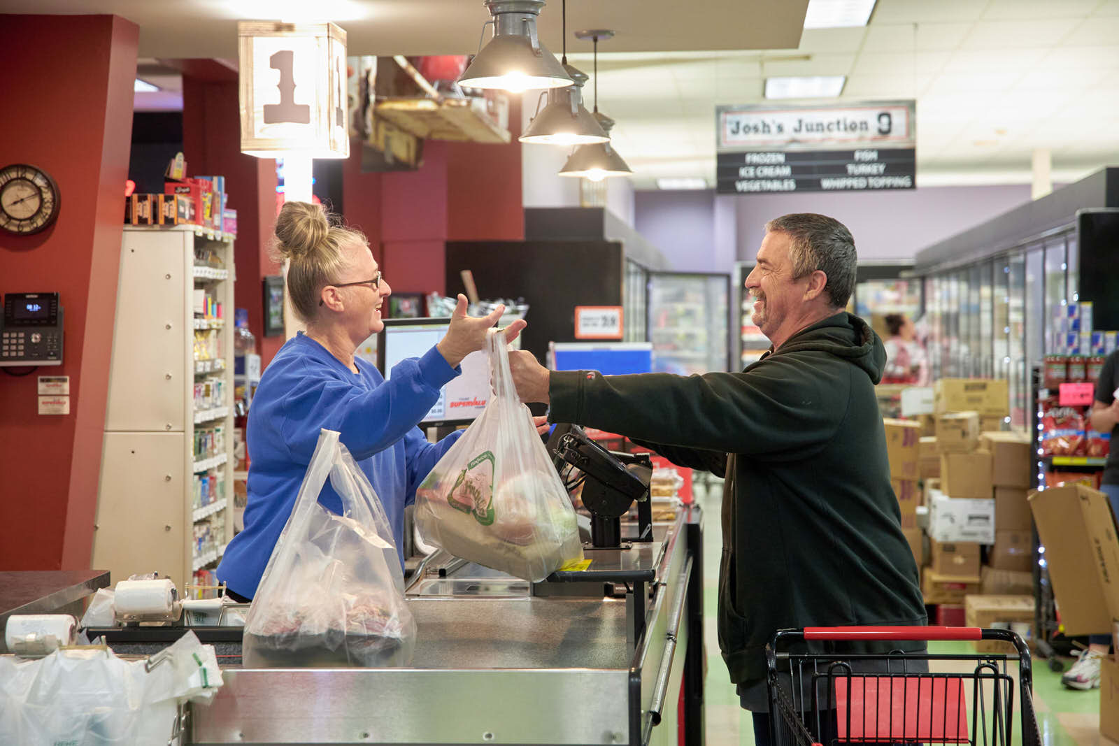 Supervalu employee handing groceries to customer at the checkout counter.