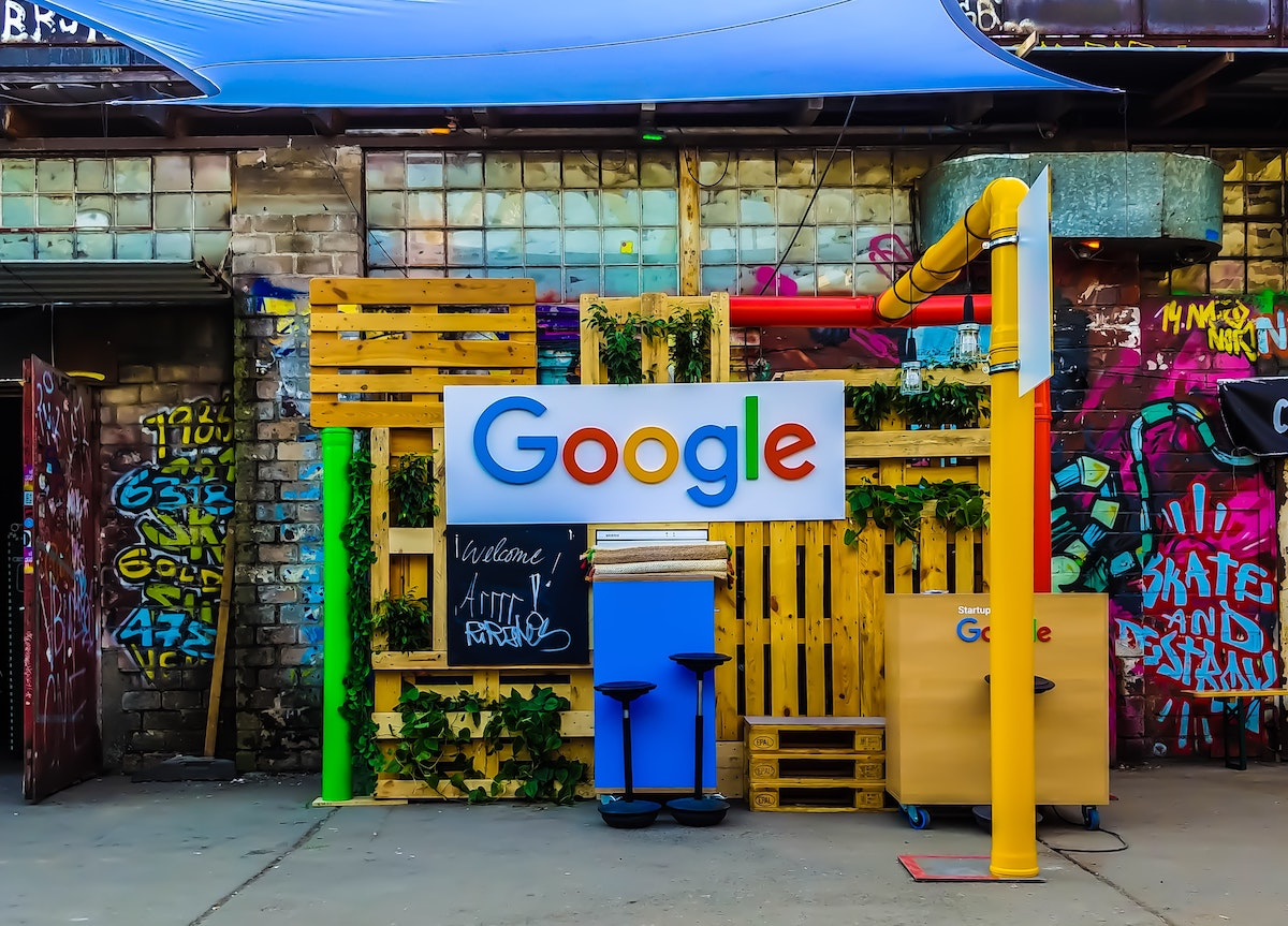 White sign with google letters infront of pipes in red, green and yellow and a graffiti background.
