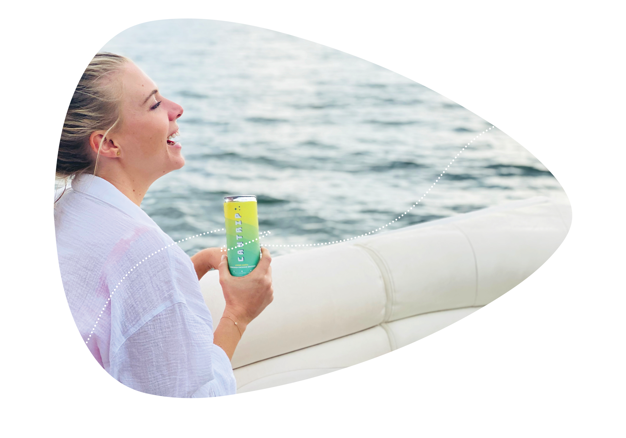 A woman smiles while she drinks a Cantrip Lemon Basil seltzer on a boat.
