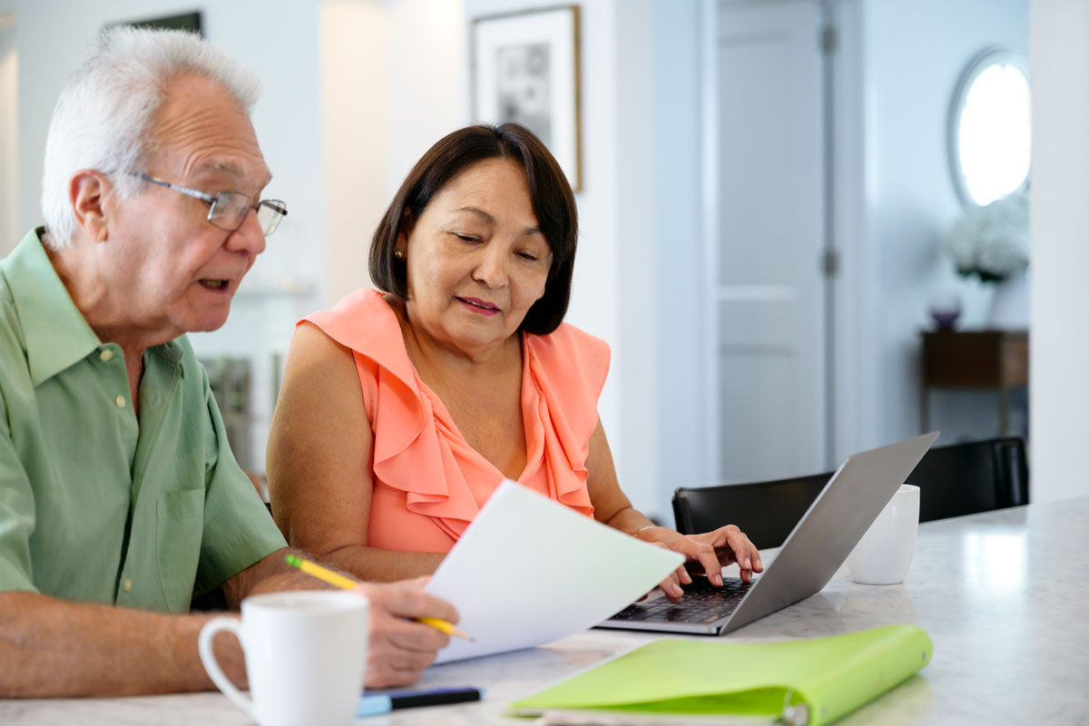 Senior couple looking at insurance paperwork and review their options