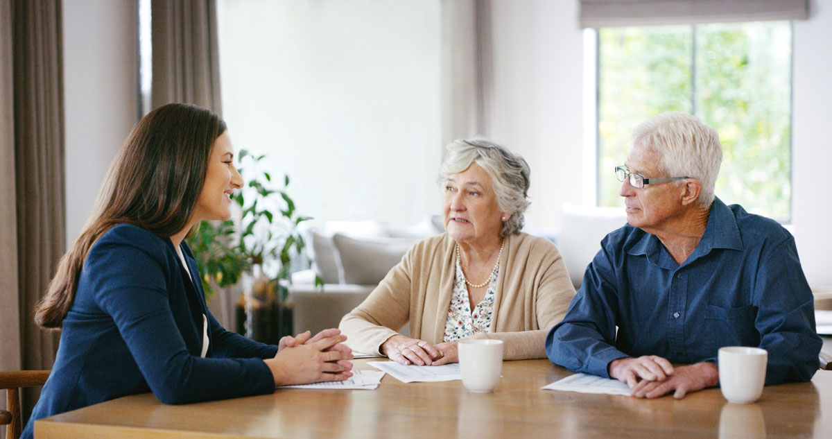 Insurance adviser speaking with senior couple about their options