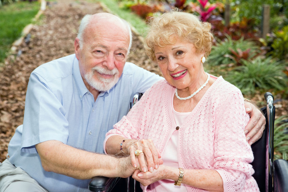 Senior husband and wife, who is in a wheelchair, relaxing in their garden