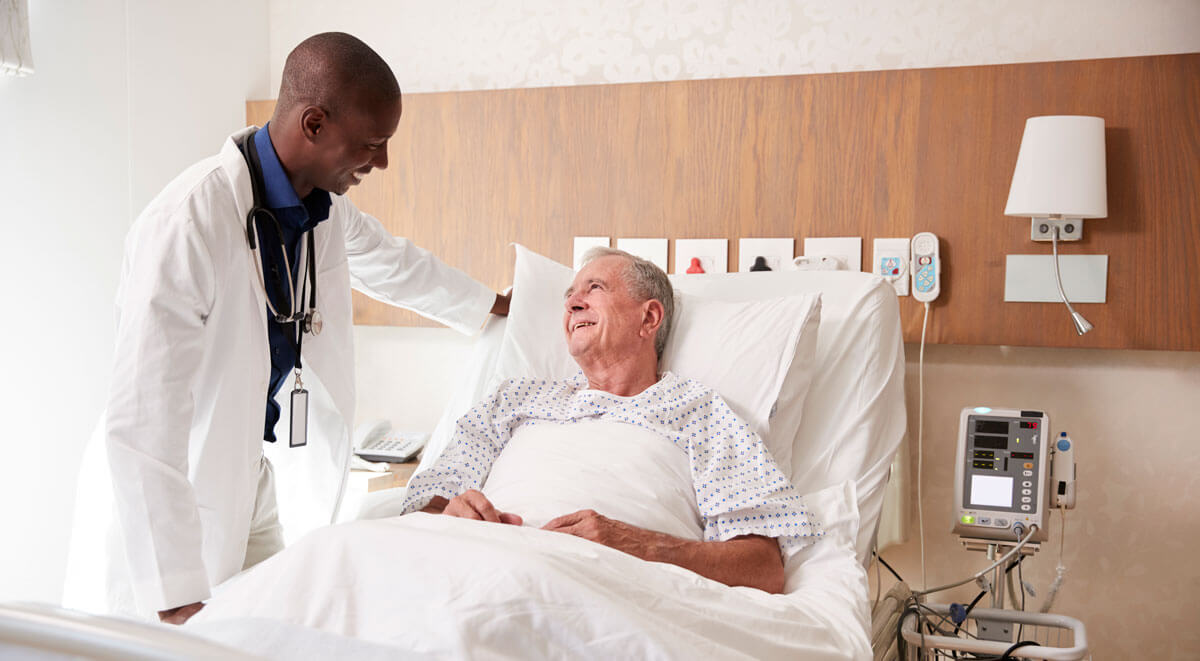 Doctor speaking with good-spirited patient in hospital bed