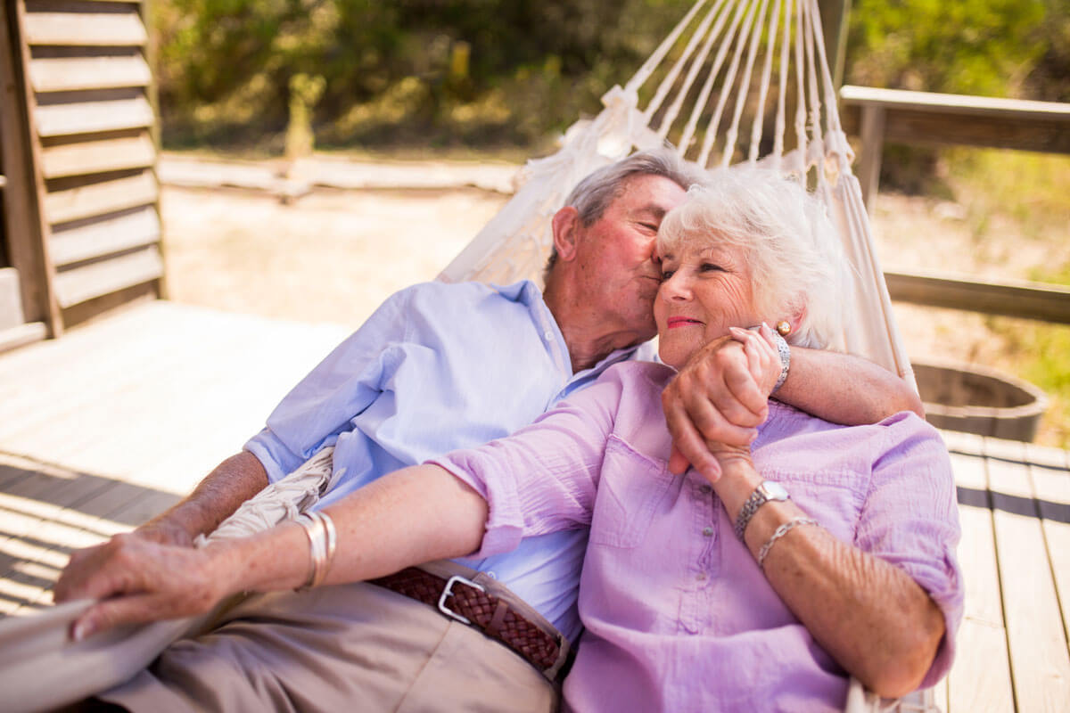Happy senior couple lounging in a hammock