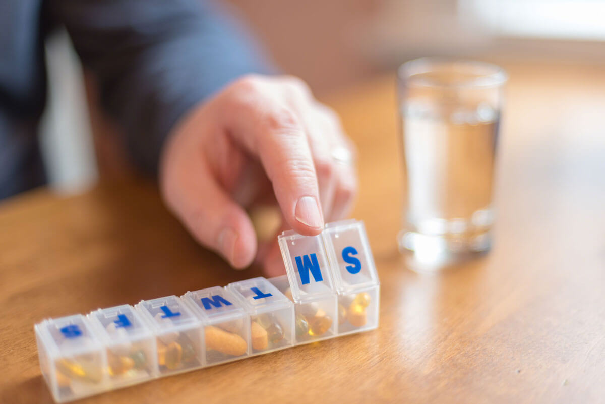 Close up of man's hand using a pill holder to organize daily medications and vitamins
