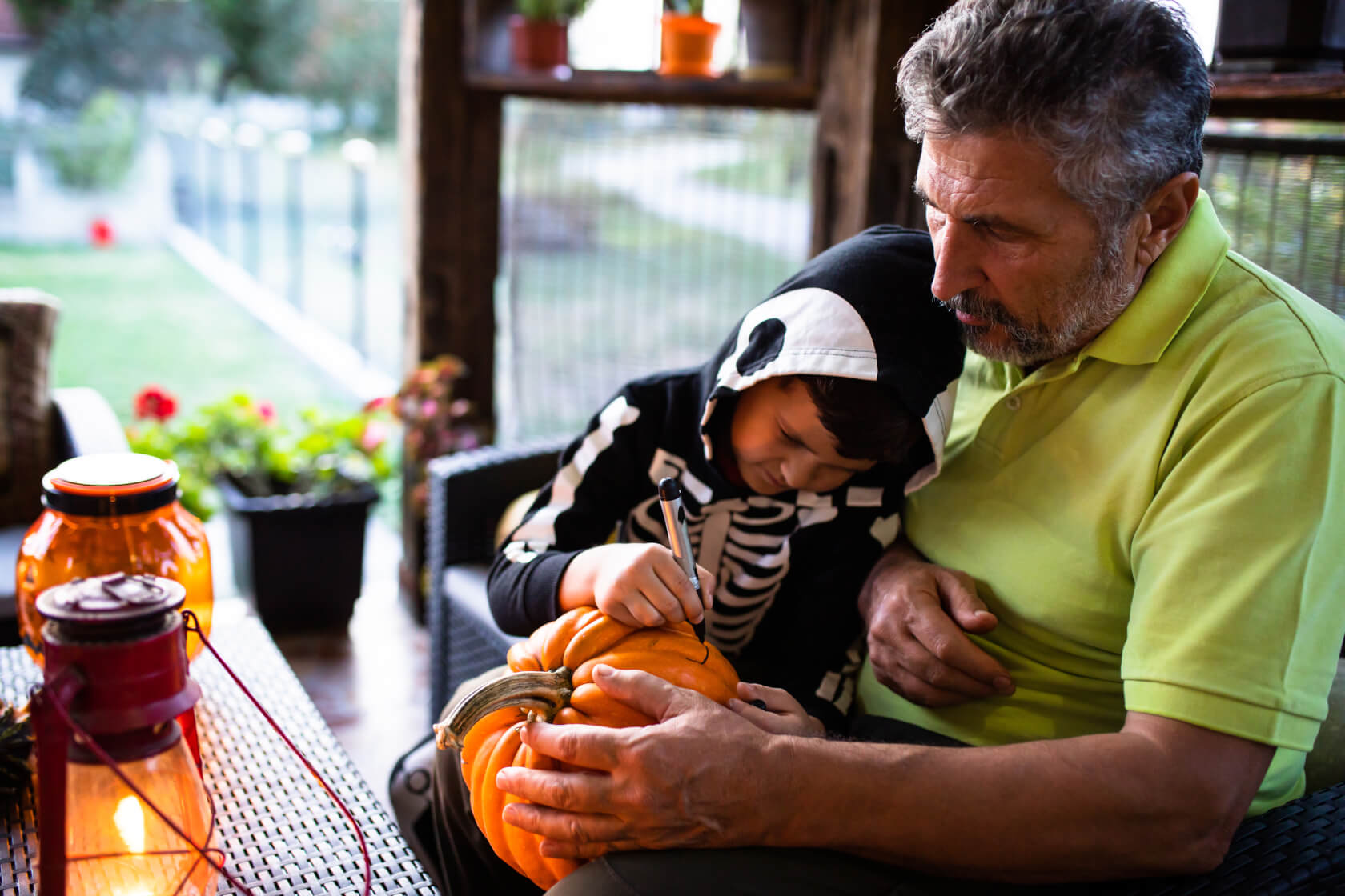 Senior man sitting with young grandson in skeleton costume, getting ready to carve a pumpkin