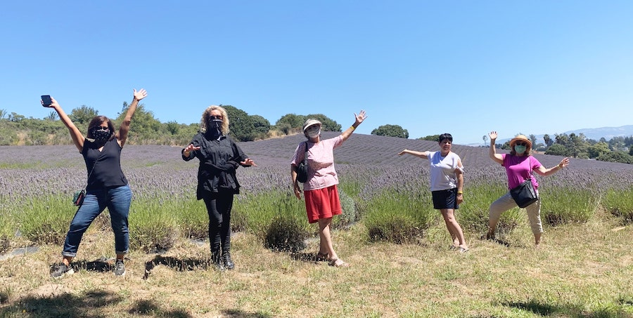 Ladies in a field wearing face masks to be safe but having fun