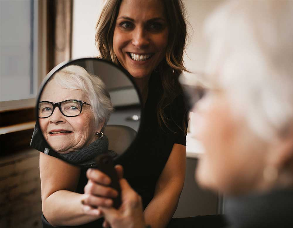 Photo of a patient looking at herself in a mirror that Dr. Graham is holding